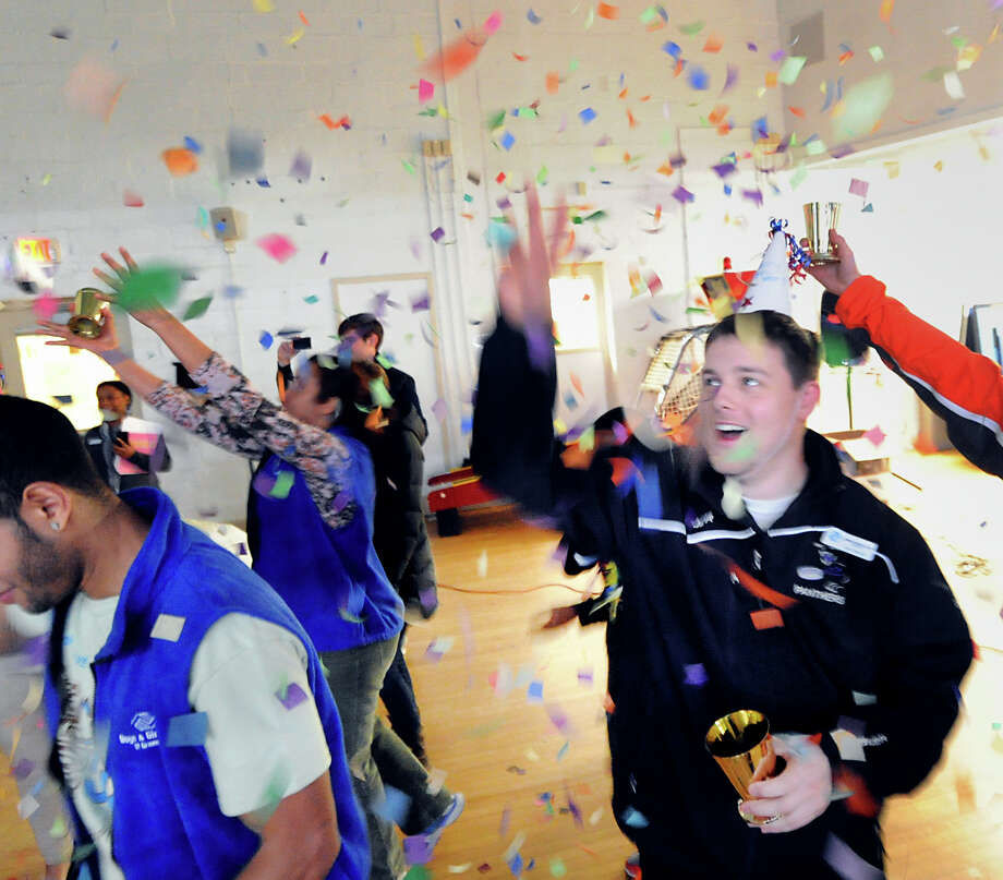 At right, Ian Tarrant, the hockey coordinator for the Boys & Girls Club of Greenwich, throws confetti during the New Year's Eve celebration at the club in Greenwich, Tuesday afternoon, Dec. 31, 2013. Photo: Bob Luckey / Greenwich Time