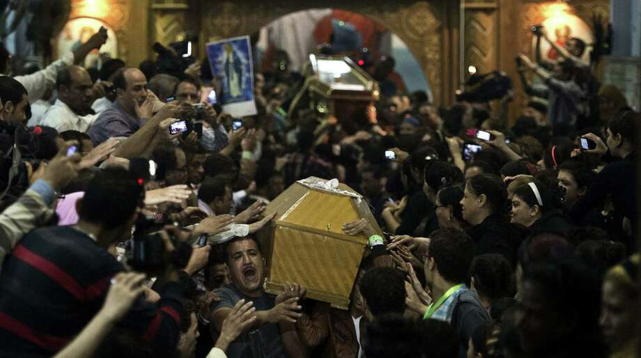 Egyptian Copts carry four coffins down the aisle of the Virgin Mary Coptic Christian church in Cairo, in October as thousands attend the funeral of the victims, gunned down as they attended a wedding the previous evening at the same church. Attacks on Christians have increased in the Middle East and North Africa. Photo: Kahled Desouki / Getty Images / AFP