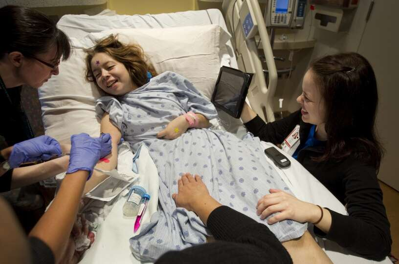 Child Life Specialist Kari Lown, right, plays music for Julia Cuevas, 15, as Dr. Lindsay Burrage, le