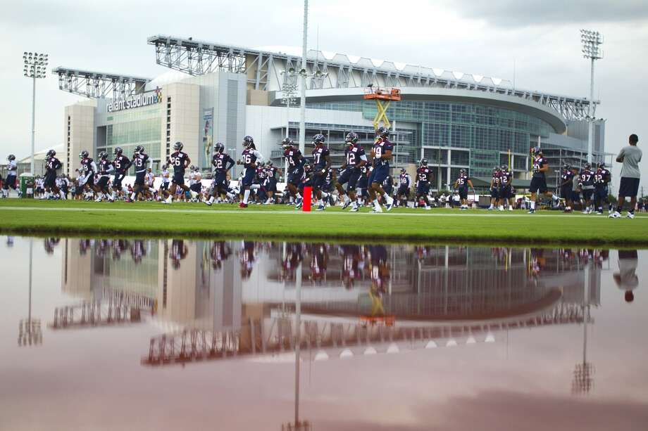 Houston Texans players and Reliant Stadium are reflected in a puddle of water next to the practice field during Texans training camp at the Methodist Training Center Saturday, July 27, 2013, in Houston. Photo: Brett Coomer, Houston Chronicle