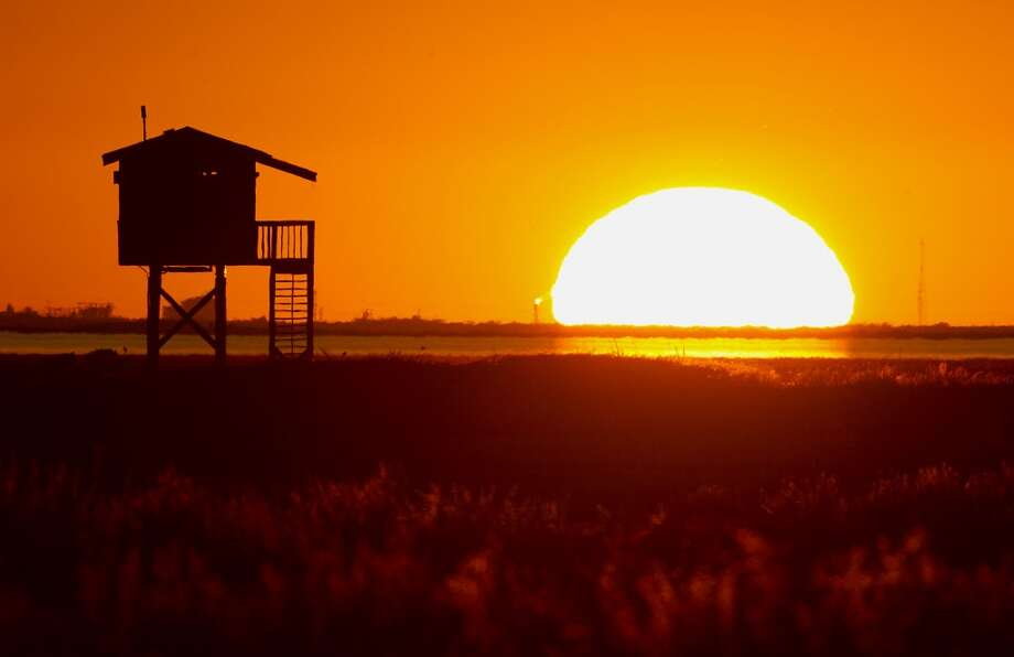 The sun sets over Christmas Bay Wednesday, Oct. 23, 2013, in Surfside. Photo: James Nielsen, Houston Chronicle