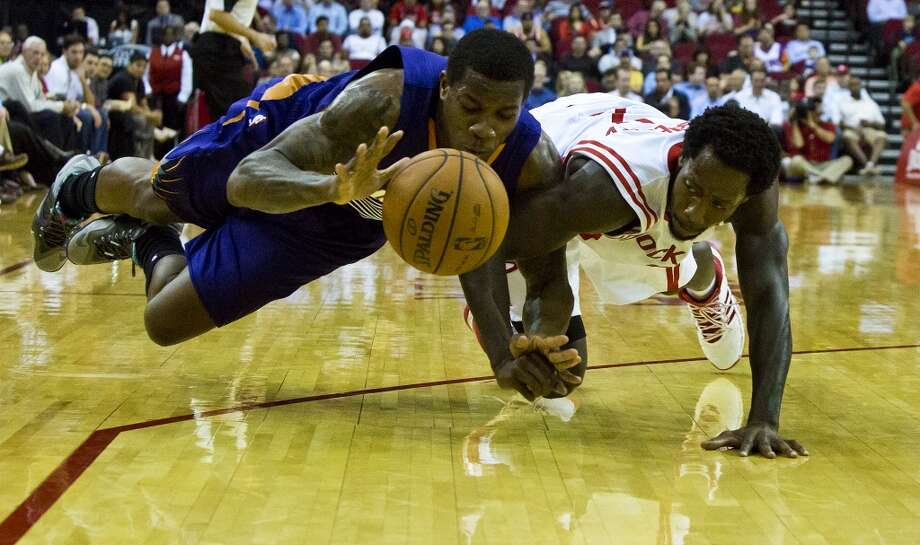 Phoenix Suns point guard Eric Bledsoe battles for the ball mid air against Houston Rockets point guard Patrick Beverley (2) early on the first period at the Toyota Center in Houston, Wednesday, Dec. 4, 2013. Photo: Marie D. De Jesus, Houston Chronicle
