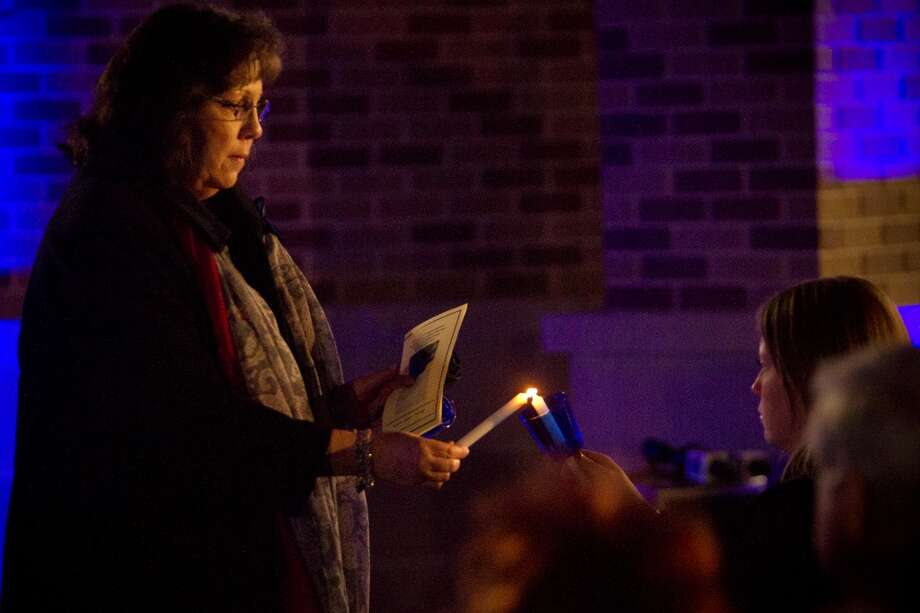Mitzie Norman, widow of slain Bellaire Police Sgt. Jimmie Norman lights her daughter's candle as a symbolic way of keeping her husband's memory and legacy alive. Monday, Dec. 23, 2013, in Bellaire. Photo: Houston Chronicle