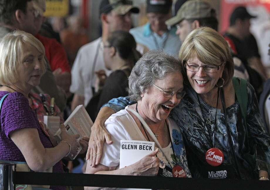 Eby Owen, center, of Dunedin, FL and Debbie Brinson, right, of San Antonio share a hug as they wait in line for the Glenn Beck book signing event during the NRA convention at the George R. Brown Convention Center  Saturday, May 4, 2013, in Houston. They woman said they became fast friends as they waiting for more than two hours. Photo: Houston Chronicle