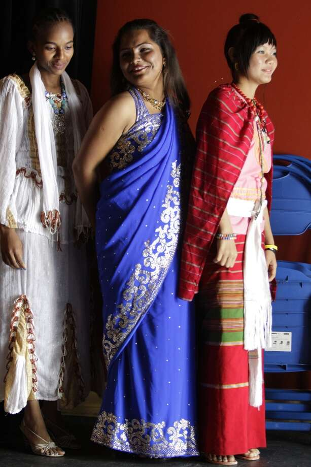 Liza Phillipo,17,  left, a refugee from Eritrea, Manja Biswa, 16, a refugee from Nepal, and Nga Meh, right, 16, a refugee from Burma, wait to go on stage in a student fashion show during the World Refugee Day celebration at  Baker-Ripley Neighborhood Center, 6500 Rookin Street  Saturday, June 15, 2013, in Houston. The students with Partnership for the Advancement & Immersion of Refugees (PAIR) wore clothing representing their home countries. The event also included cultural performances, children's activities,  community resource fair, art and educational exhibits. Photo: Houston Chronicle