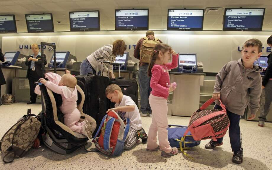 Marilynne Zborowski, of The Woodlands, and her husband, Justin Zborowski, check in for their flight in Terminal C at George Bush Intercontinental Airport along with their daughters Emma Zborowski, 14-months-old, left, and Violet Zborowski, 4, and nephews, Christian Taylor, 4, and Stephen Taylor, 6, right, Monday, Nov. 25, 2013, in Houston. The kids will be spending Thanksgiving at their grandmother's house in Arizona. Photo: Melissa Phillip, Houston Chronicle