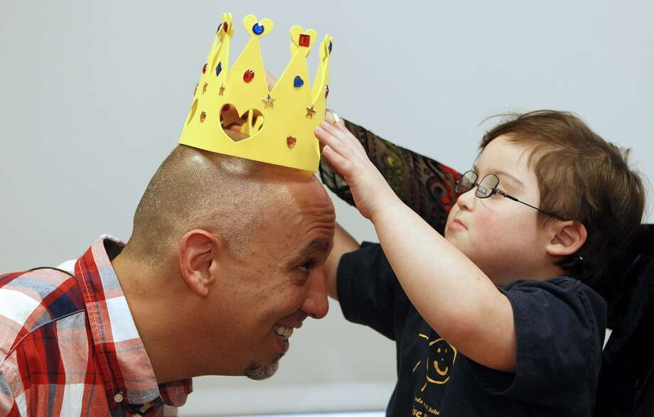 Waiter Michael Garcia has a crown placed on his head by his new friend, 5-year-old Milo Castillo, after students and teachers from The Rise School of Houston honored Garcia for standing up for their classmate Milo Wednesday, Feb. 6, 2013, in Houston. Michael Garcia, a waiter at Laurenzo's restaurant, refused to serve a couple who make a rude remark about Milo being a special needs child.  Photo: Johnny Hanson, Associated Press