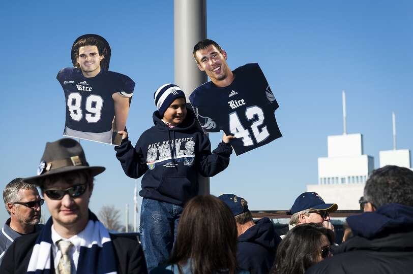 A fan holds up cutouts of Rice wide receiver Christian Fletcher (89) and linebacker Michael Kutzler