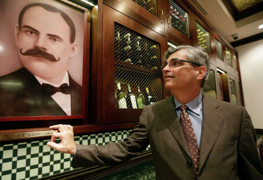 In this Tuesday, Oct. 22, 2013 photo, Stephen Sawitz, co-owner of Joe's Stone Crab restaurant , stands next to a photograph of his great-grandfather Joe Weiss, the founder of Joe's, at the restaurant in Miami Beach, Fla. Joe's Stone Crab has been family-owned from the start when it opened in 1913 as a mom-and-pop fish house. Today, it's a must-stop spot where wearing a bib over fine-dining attire is the norm. (AP Photo/Lynne Sladky) ORG XMIT: MER2013123014023546 Photo: Lynne Sladky / AP