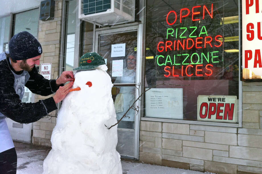 John Modzelewski, an employee at Franco's Pizza, puts the finishing touches on a pizza snowman he made with co-worker Dan Ourfalian, not pictured, in front of the shop in Milford Conn. on Friday February 8, 2013. Looking on in the doorway is owner Franco Patrizi. Note the pepperonis John used for the snowman's eyes. Photo: Christian Abraham / Connecticut Post