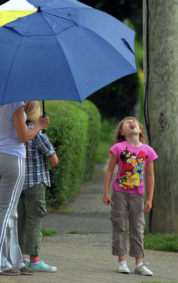 Varleria Carbone, 7, catches raindrops on her tounge while waiting for her friends to come home from school at the bus stop along Oldfield Road in Fairfield, Conn. on Tuesday June 11, 2013. Photo: Christian Abraham / Connecticut Post