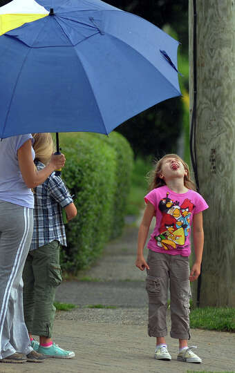 Varleria Carbone, 7, catches raindrops on her tounge while waiting for her friends to come home from