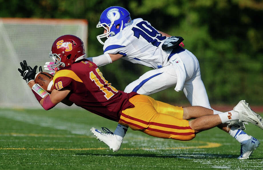 St. Joseph's Alex Pinto attempts to intercept a pass intended for Darien's Griffin Ross, during high school football action in Trumbull, Conn. on Saturday October 5, 2013. Pinto fumbled the ball. Photo: Christian Abraham / Connecticut Post