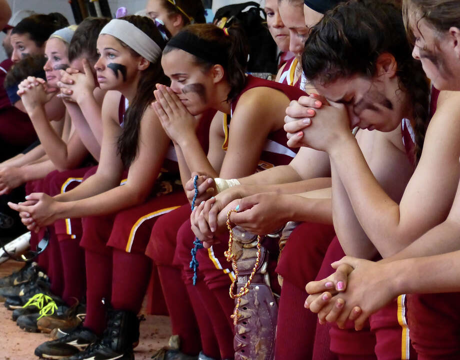 St. Jospeph team members pray during a rain delay, during FCIAC Softball Championship action against New Canaan in Fairfield, Conn. on Thursday May 23, 2013. If the game was called due to rain, the team would have lost to New Canaan. After resuming play St. Joseph was unable to surmount New Canaan's lead, losing 2-1. Photo: Christian Abraham / Connecticut Post