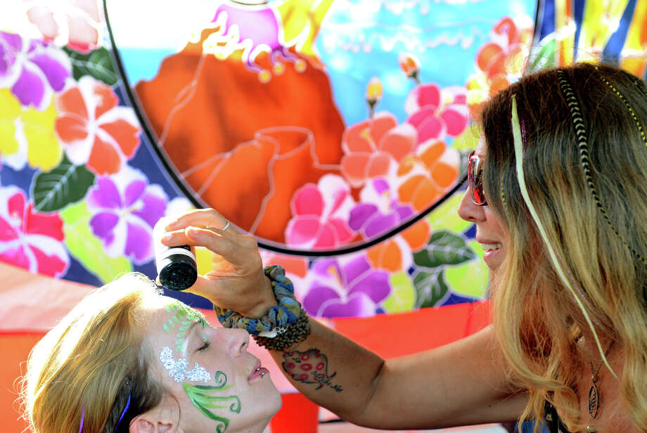Ali Chambliss applies glitter to Colette Tomolonis, of Brattleboro, VT, at 18th Annual Gathering of the Vibes music festival at Seaside Park in Bridgeport, Conn. on Friday July 26, 2013. Photo: Christian Abraham / Connecticut Post freelance
