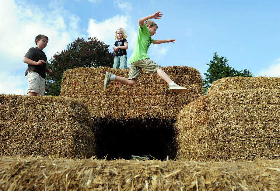 Charlie Capite, 7, of Shelton, leaps over hay bales set up for the kids at Benedict's Home and Garden in Monroe, Conn. on Wednesday October 2, 2013. Benedict's is a family owned business that has been serving the area for over 50 years. Photo: Christian Abraham / Connecticut Post