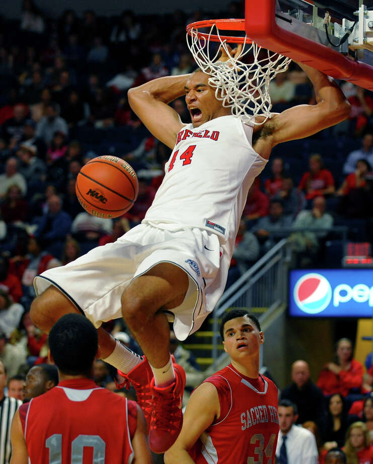 Fairfield University's Malcolm Gilbert slam dunks the ball, during 2013 Connecticut 6 Classic men's basketball action against Sacred Heart University at the Webster Bank Arena in downtown Bridgeport, Conn. on Saturday November 9, 2013. Photo: Christian Abraham / Connecticut Post