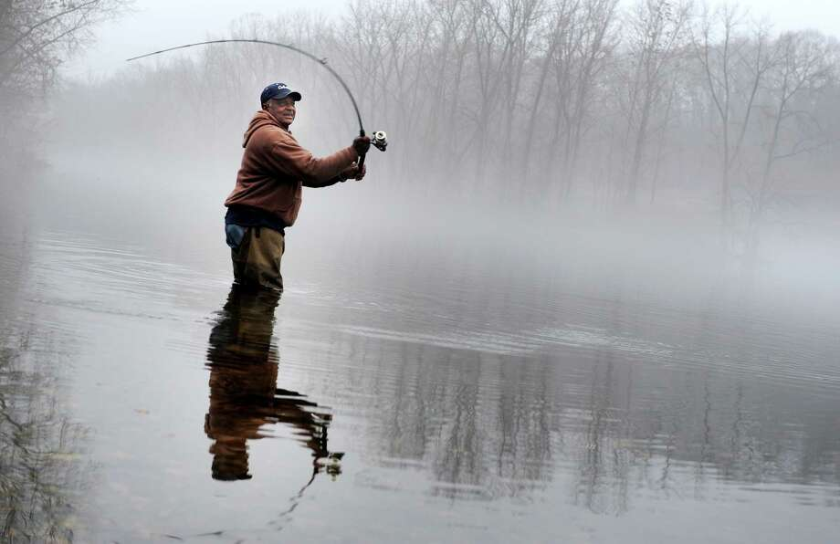 Anderson Bish, of Bridgeport, casts his line into a fog-laden Housatonic River Thursday, Dec. 5, 2013 at the Derby Dam in Derby, Conn. Photo: Autumn Driscoll / Connecticut Post