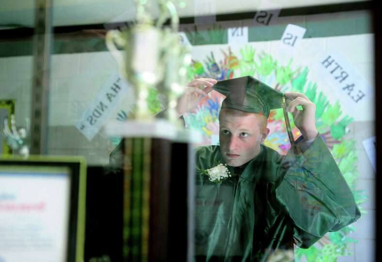 Maverick Taramelli, of Shelton, straightens his cap before the Emmett O'Brien Technical High School