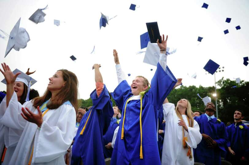 Graduate Matt Nolting, center, throws up his cap during commencement at Bunnell High School in Strat