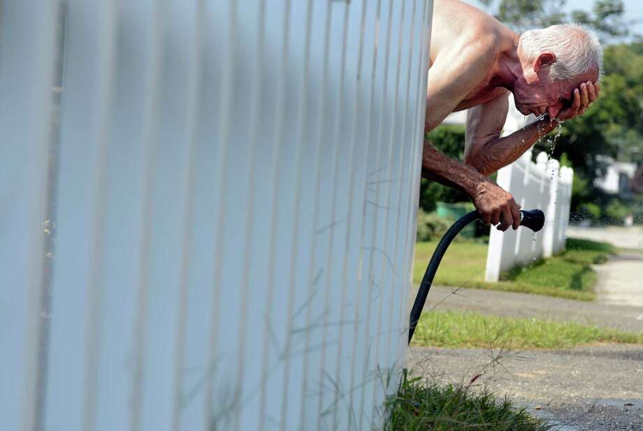 Sibin Sieluo cools off in his garden hose after a morning of yard work in above 90 degree temperatures Wednesday, September 11, 2013 at his home in Derby, Conn. Photo: Autumn Driscoll / Connecticut Post