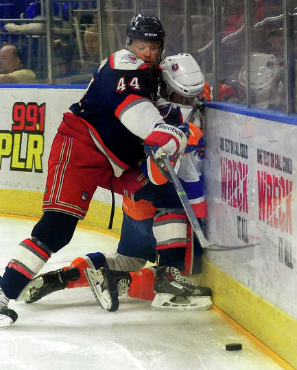 Hartford's Aaron Johnson checks Sound Tigers Riley Wetmore into the boards, during hockey action at