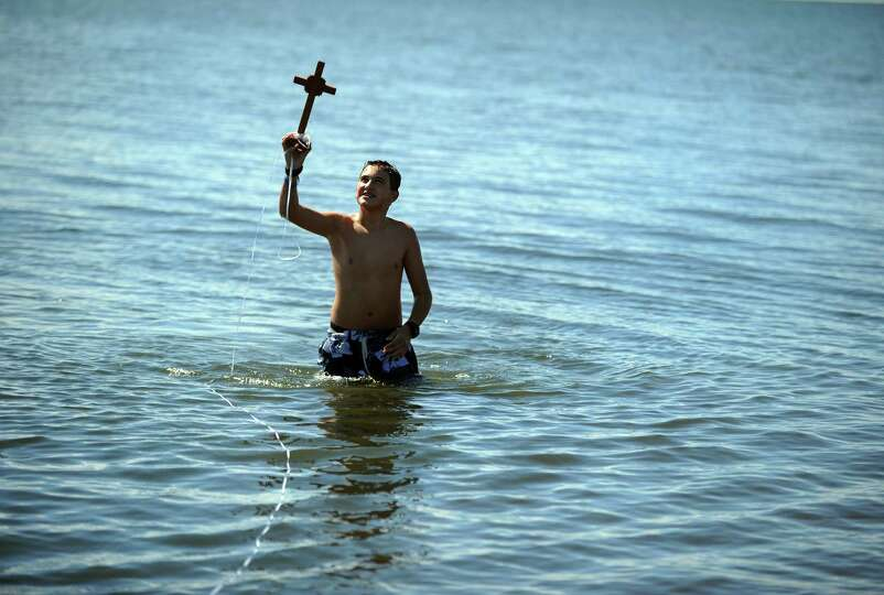 Fourteen-year-old Christos Koutsitzis, of Trumbull, retrieves a crucifix from the Long Island Sound