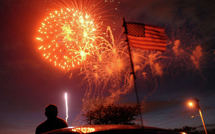 A spectator watches the fireworks display at Short Beach in Stratford, Conn. on Wednesday July 3, 20