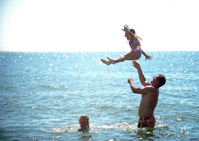 Andrew Hurlbut throws his 6-year-old daughter Lucy up in the air as they play and swim in the Long I
