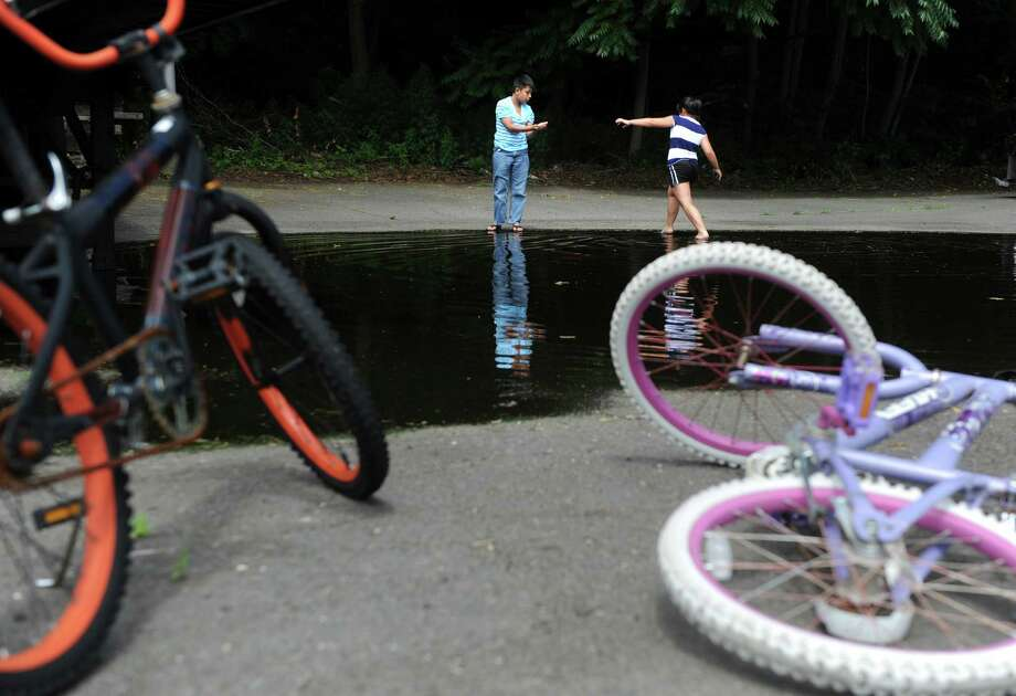 Friends Estefano Torres, 11, and Arlinda Komani, 9, of Derby, look for tadpoles while they cool off in a large puddle off Park Avenue in Derby, Conn. following an afternoon of bike riding around the neighborhood Wednesday, July 3, 2013. Photo: Autumn Driscoll / Connecticut Post