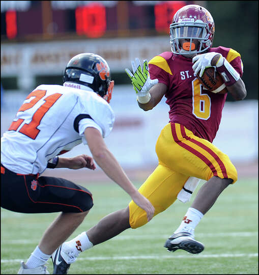 St.Joseph's Mufasha Abdul Basir gets ready to stiff arm Ridgefield's Robert Peckham Saturday, Sept.