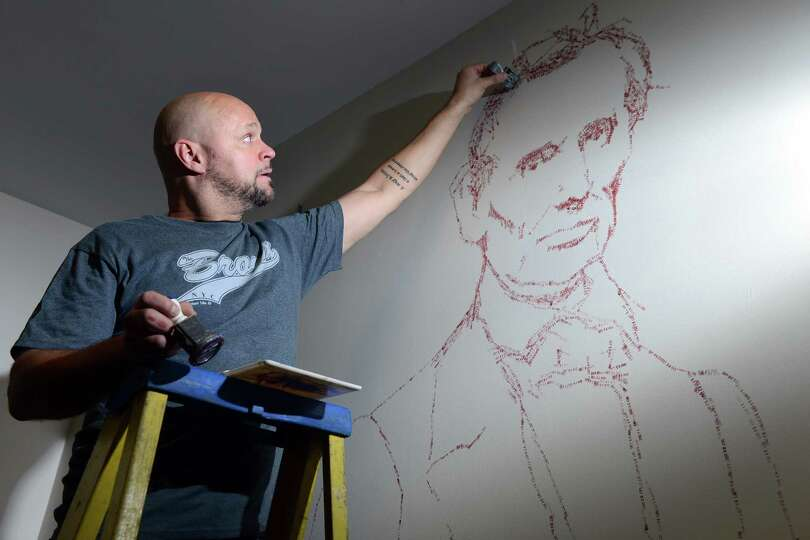 Artist Roberto Martinez creates the image of Abraham Lincoln out of time stamps in the vault on the