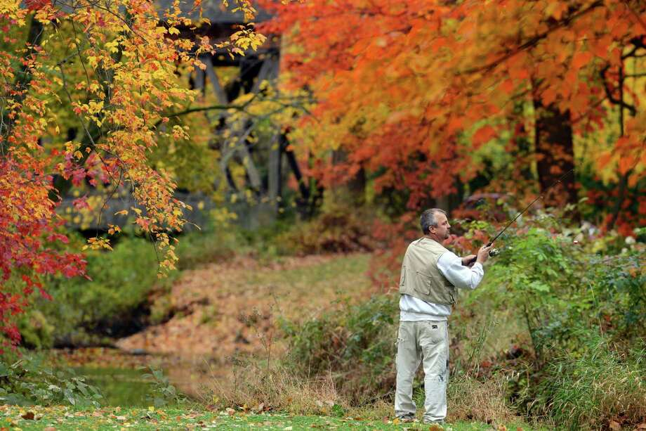 Paul Hurteau, of Trumbull, fishes for trout in the Pequonnock River after the weather cleared up on Friday, Nov. 1, 2013 at Twin Brooks Park in Trumbull, Conn. A quick moving cold front brought strong winds and some rain to southwestern Connecticut late Friday morning, with gusts to nearly 30 mph, but the sky brightened by mid-afternoon. Photo: Autumn Driscoll / Connecticut Post