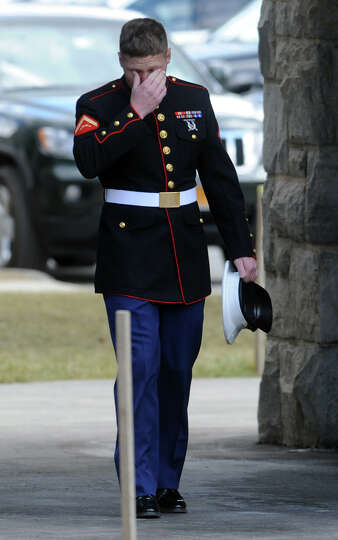 A lone Marine steps outside of St Ann's Church during the funeral service for Marine Lance Cpl. Roge