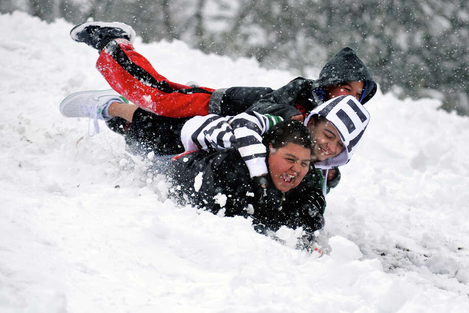 Jason Miranda, bottom, Christian Perez, center, and Javier Alamo, top, sled down a hill in Beardsley Park, in Bridgeport, Conn., March 18th, 2013. Photo: Ned Gerard / Connecticut Post
