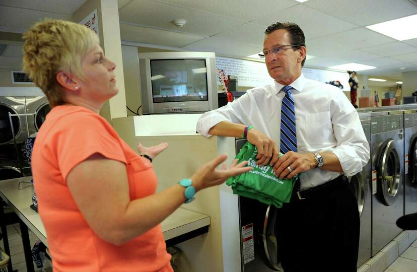 Sharon Doherty, owner of P.J.'s Laundramat in Sandy Hook, talks with Governor Dannel P. Malloy durin