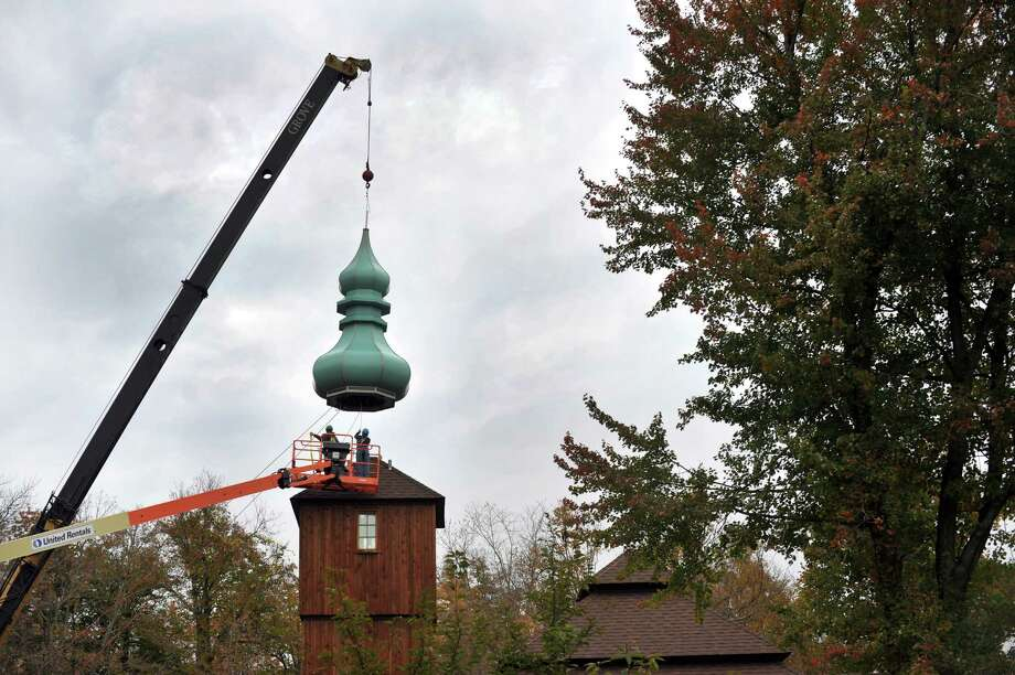 Holy Trinity Orthodox Church, on Joe's Hill Road in Danbury, Conn., raised a new cupola atop the church Wednesday, Oct. 16, 2013. Father Luke Mihaly, church pastor, said the 27 feet cupola,  symbolizes a flame of prayer. The green cupola, the color representing the Holy Spirt and life, is the first of three to adorn the church. Holy Trinity moved from its original  site on Eighth and Roberts Avenue to this new church building in 2007. Photo: Carol Kaliff / The News-Times