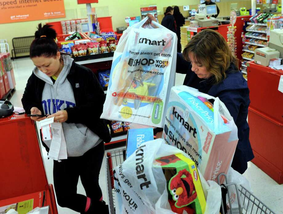 Holly Scanlon, 29, got to Kmart in Southbury, Conn. at 5:30 a.m., to be in time for the store's 6 a.m. opening on Thanksgiving Day, Nov. 28, 2013. Christmas shopping for her two young children, she checks her receipts as sales clerk Terri Ames loads her cart. Photo: Carol Kaliff / The News-Times