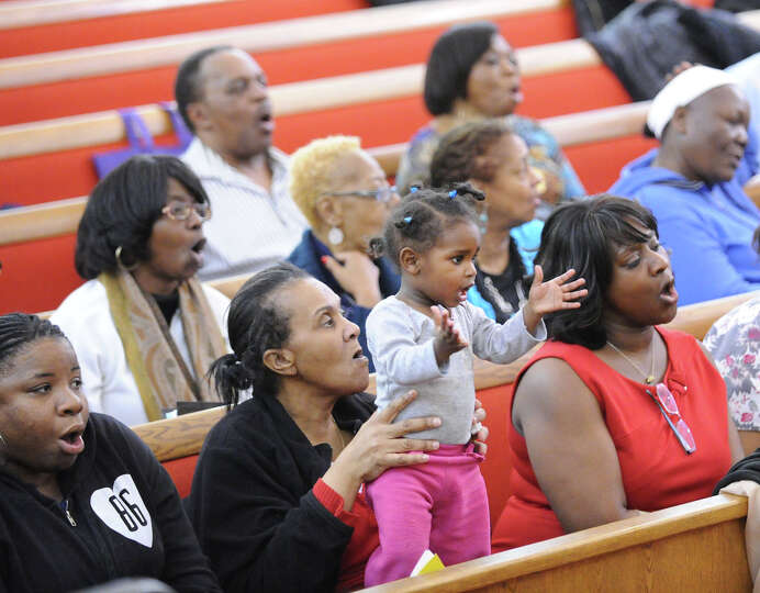Chrystrean Francis, 15 months old, is held by her mother Patricia Thompson, while clapping her hands