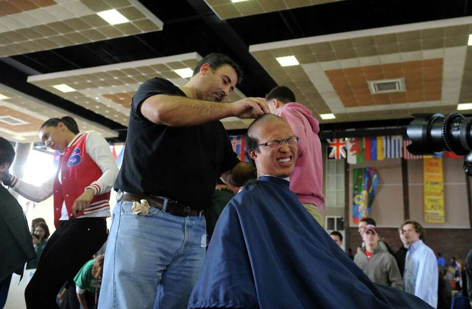 Eric Alfano shaves Charles Lok, 17, at the St. Baldrick Foundation, a benefit to find cures for childhood cancers in the Student Center, at Greenwich High School, Greenwich,  Conn., Thursday, March 28, 2013. Photo: Helen Neafsey / Greenwich Time