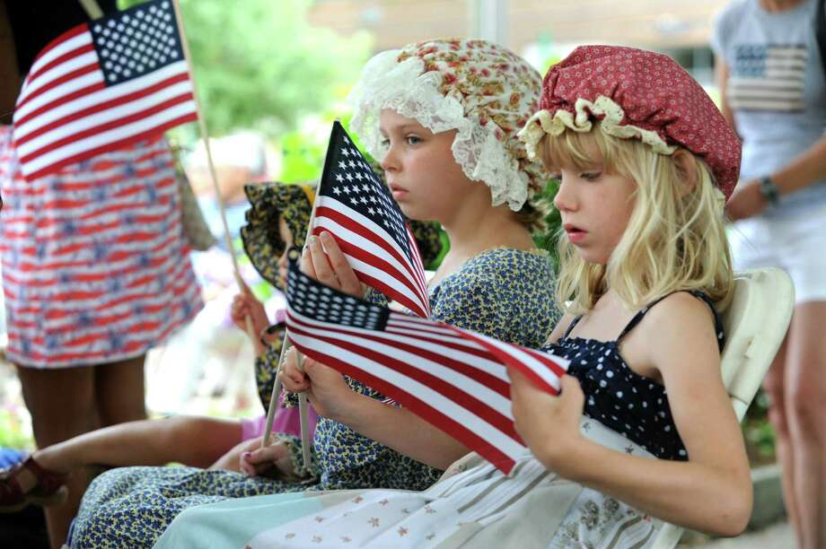 Emma Woodruff, 9, left, and her sister Abigail, 6, of the children of the American Revolution, hold flags at the Fourth of July ceremony at Greenwich Town Hall,  in Greenwich, Conn., Thursday, July 4, 2013. Photo: Helen Neafsey / Greenwich Time