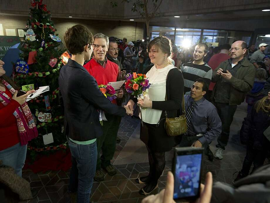 Natalie Dicou (left) and Nicole Christensen are married by Salt Lake City Mayor Ralph Becker on Dec. 20. The state is seeking a stay on such weddings. Photo: Kim Raff, Associated Press