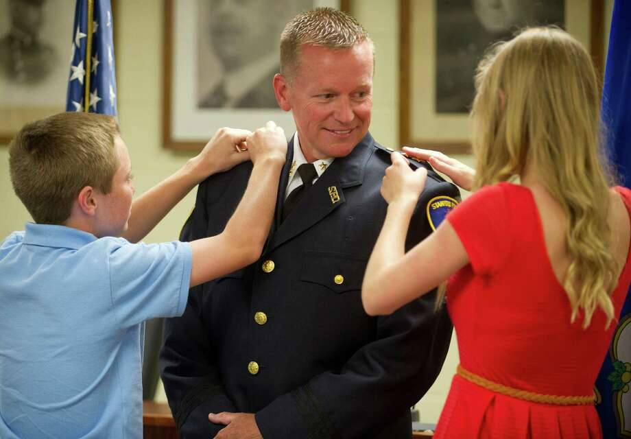 Timothy Shaw's daughter, Taylor, 16, right, and son, Ryan, 13, left, pin stars to his shoulders as he is sworn in as Assistant Police Chief at Stamford police headquarters on Wednesday, June 12, 2013. Photo: Lindsay Perry / Stamford Advocate