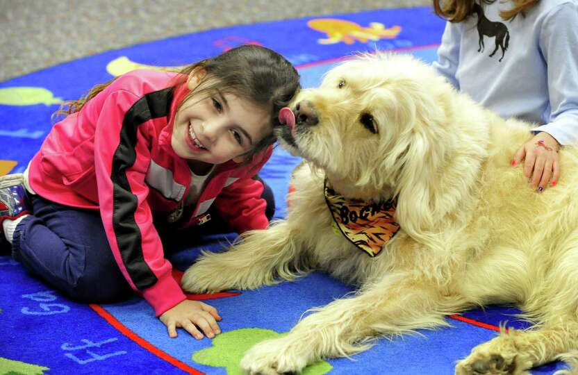 Lucia Rose St.Lorenzo, 5, gets a wet kiss from Bocker, the famous Labradoodle, during a visit to the