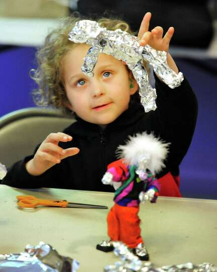 Lilly Hunter, 5, holds up her sculpture during a program titled