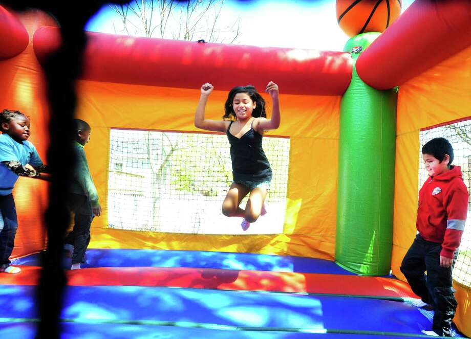 Alezandra Molina, 9, has serious fun in the bouncy house as the Boughton Street Branch of the Regional YMCA of Western Connecticut jumpes into summer by celebrating Healthy Kids Day in Danbury, Conn. Saturday, April 27, 2013. Photo: Michael Duffy / The News-Times
