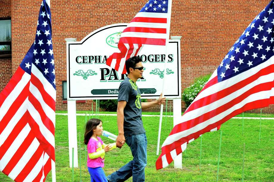 "Campbell Juan, 4, and her dad, Emmanue,l help the Kiwanis Club of Greater Danbury Foundation puts up a ""Field of Honor"" of 200 American Flags to honor veterans at the War Memorial in Danbury, Conn. Saturday, May 18, 2013. Photo: Michael Duffy / The News-Times"