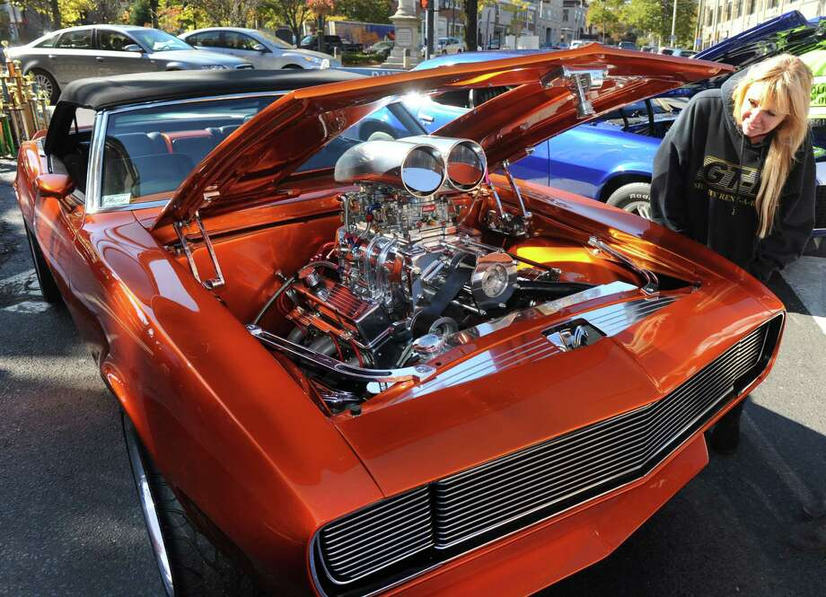 "Denise Rafferty looks over a 1968 Chevy Camero during a "" Classic Car & Bike Show on Main Street""  in Danbury, Conn. Sunday, Oct. 20, 2013. In the tradition of previous ""Karing for Kelly"" events, the charity event is hosted by Lew Lombardo's Ultimate Restorations LLC, and George Korres's Nico's Pizza and Pasta, to benefit Danbury firefighter Joe LaDuca, who is suffering malignant brain tumors. Photo: Michael Duffy / The News-Times"