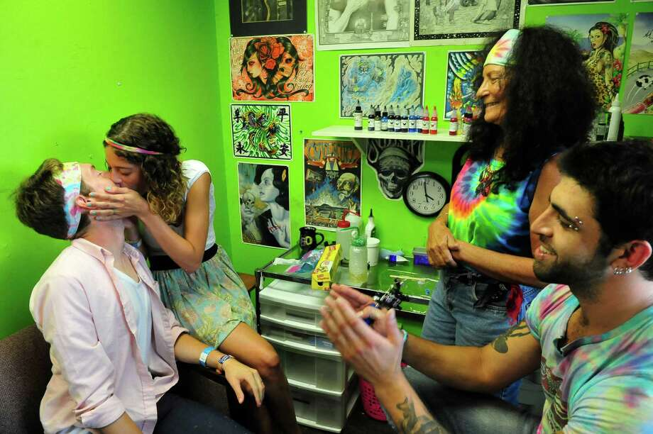 Joseph New, 20, of New Fairfield, left, and Mollie Maturah, 19, of Andover, Mass., are tattooed and married at The Iron Butterfly, in Danbury, Conn. Friday, Aug. 12, 2013. Annette Matthews, the tattoo parlor owner, is also a justice of the peace and performed the ceremony. The couple read their vows as tattoo artist Mathew Leibowitz, right, tattooed the rings on their fingers. Photo: Michael Duffy / The News-Times
