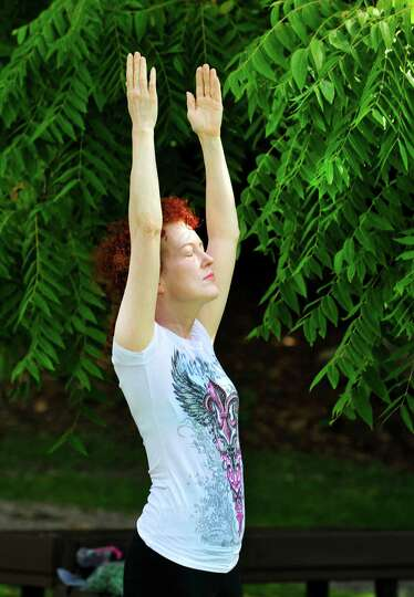 Sheila Bonnabeau practices her upward salute during Yoga at Tarrywile, in Danbury, Conn. Sunday, Aug
